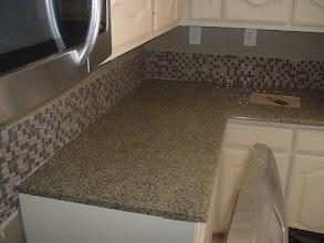 Photo: 1x1 glass tile installation on wall as backslash granite counter top