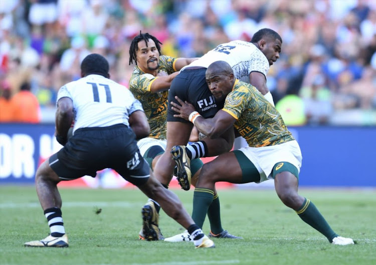 Vatemo Ravouvou of Fiji offloads while being tackled by Siviwe Soyizwapi of SA during day 2 of the HSBC Cape Town Sevens match 39, Cup Semi Final match between SA vs Fiji at Cape Town Stadium on December 9 2018.