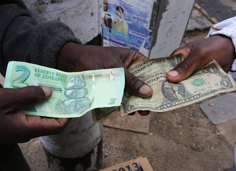 Illegal money changers pose while exchanging a new Zimbabwe bond note, left, and US dollar notes in the capital Harare. Picture: REUTERS