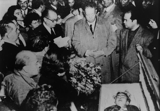 Diego Rivera next to Frida's coffin at the Palacio de Bellas Artes (Palace of Fine Arts). With him are Andrés Iduarte, who read the funeral prayer, Lázaro Cárdenas, Emma Hurtado, and Víctor Manuel Villaseñor. In the foreground is his daughter Lupe Rivera Marín.