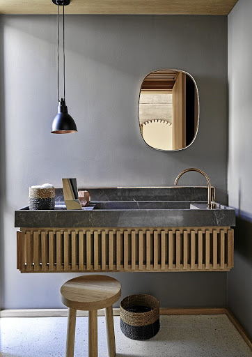 The guest bathroom reprises the pattern of vertical wooden slats found throughout the house.