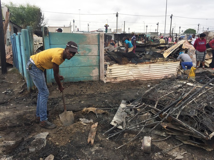Unathi Lingela clears his plot to start rebuilding his shack after a fire destroyed 100 shacks in Doornbach informal settlement on Tuesday morning. .