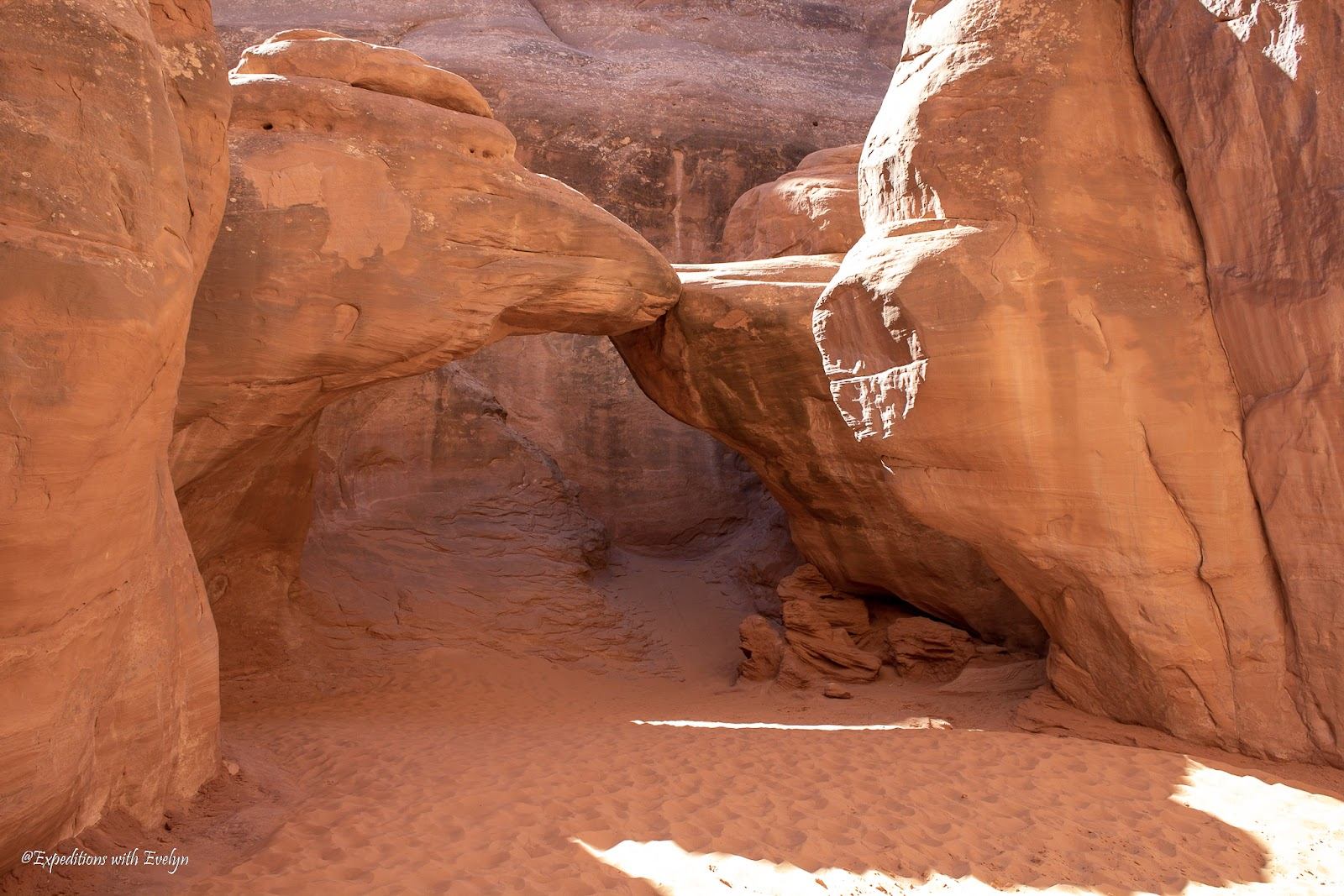 An arch of sandstone is set in canyon atop a flat surface of sand in the afternoon light.