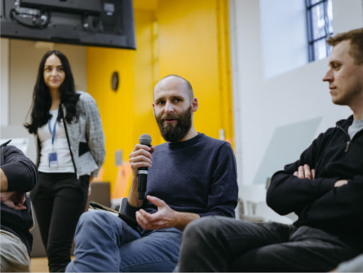 A man with a beard is speaking into a microphone. Two men and a woman are looking at him, smiling.
