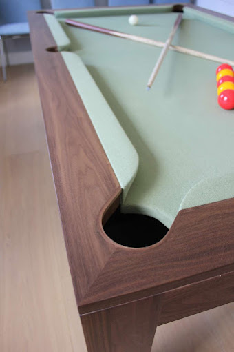 Pool Cues and snooker balls on a Refined Pool Table with Green Felt