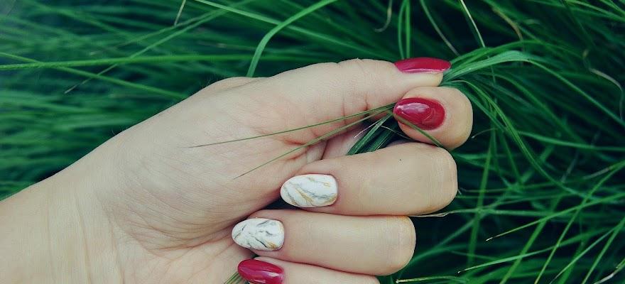 Dłoń kobiety czerwone paznokcie na tle trawy
