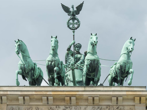 "horses-chariot-eagle-atop-brandenburg-gate.jpg -   Brandenburg Gate is topped off with a statue known as the ""Quadriga,"" a statue of the goddess of victory driving a chariot pulled by four horses."