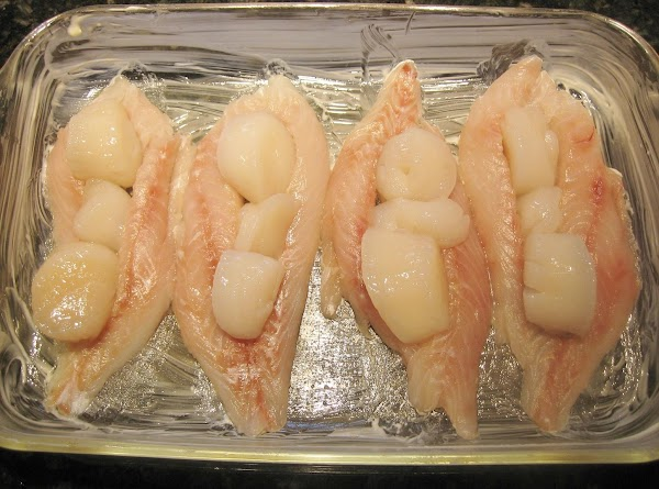 Cut a slit in middle of grouper & stuff with scallops, put into baking...