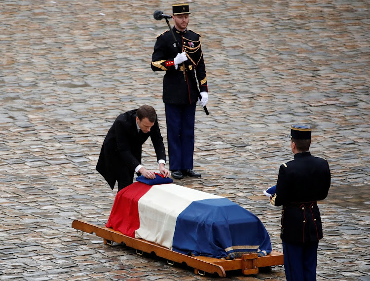 French President Emmanuel Macron honours the flag-drapped coffin of late Col Arnaud Beltrame in Paris, France, March 28, 2018. Picture: REUTERS