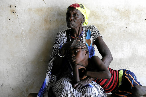 A woman comforts her son who is suffering from malaria as they wait for treatment at a Medecins Sans Frontieres-run clinic in South Sudan./REUTERS