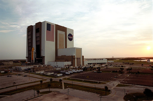 The sun is rising over the Atlantic Ocean right as Shuttle Atlantis sits outside the Vehicle Assembly Building.