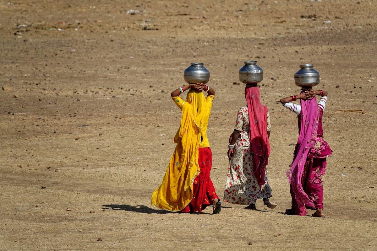 India. Rajasthan Thar Desert Camel Trek. Women bringing water back to the village