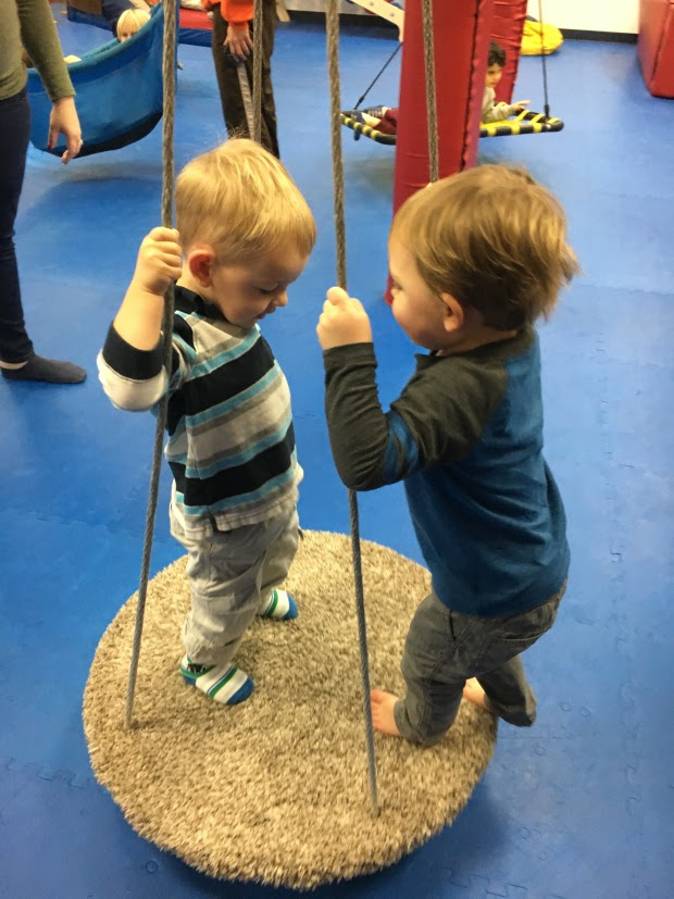 Two toddlers playing on a platform swing