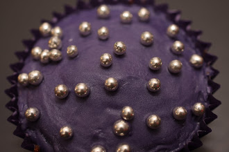 Photo: A cupcake decorated with deep purple icing and silver balls