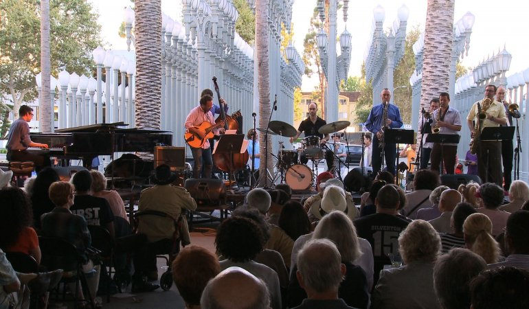 A jazz band performers for ran audience in front of Urban Light.