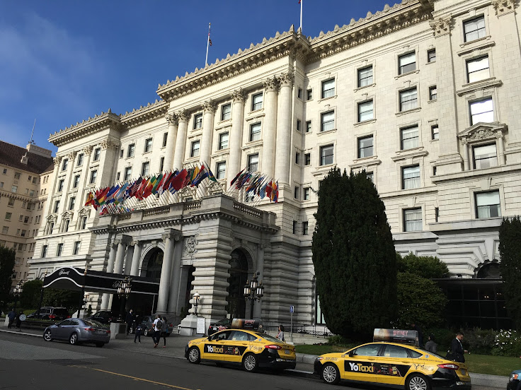 The front facade of the Fairmont Hotel, with state flags representing the signatories of the United Nations charter.