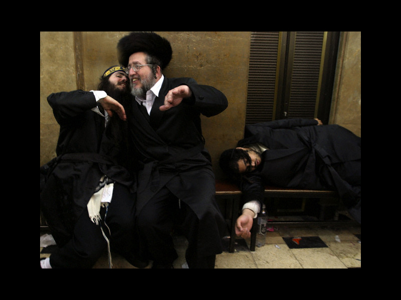 Photo: 27 Mar 2005, JERUSALEM, Israel --- Ultra-Orthodox Hasidic Jews, members of a devout Jewish sect, gesture merrily after drinking during the celebrate of the Jewish Purim holiday at a synagogue in the Mea Shearim neighborhood in Jerusalem, March 27, 2005. Purim is a carnival-like celebration which commemorates the deliverance of the Persian Jews from a general massacre.    --- Image by © Gil Cohen Magen/Reuters/Corbis