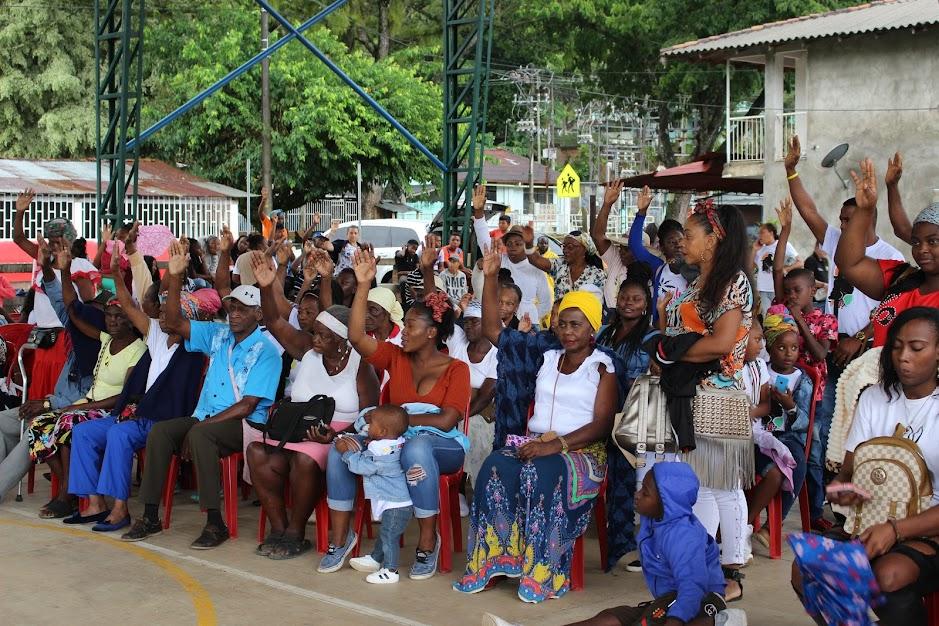 Un grupo, con mayores y madres en primera línea, levanta la mano en un ejercicio de identidad y compromiso en la conferencia del p. Venanzio Mwangi en las fiestas de Asnazú.