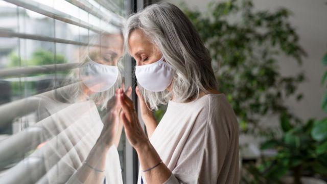 Женщина в маске у окна - стоковое фото