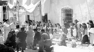 Procesión del Corpus en Turre en el año 1954. Los niños, arrodillados a su manera, asisten con extrañeza al ritual dirigido por don Manuel Sánchez.
