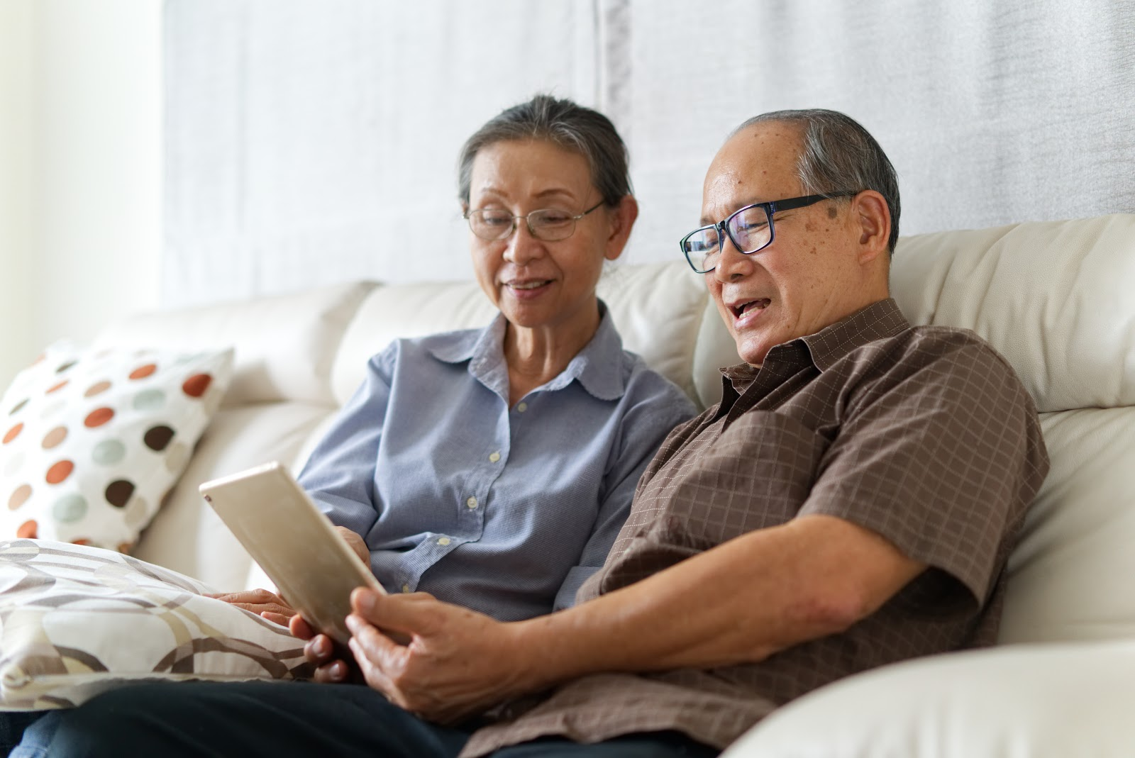 Smiling senior couple sitting on a couch while looking at a tablet