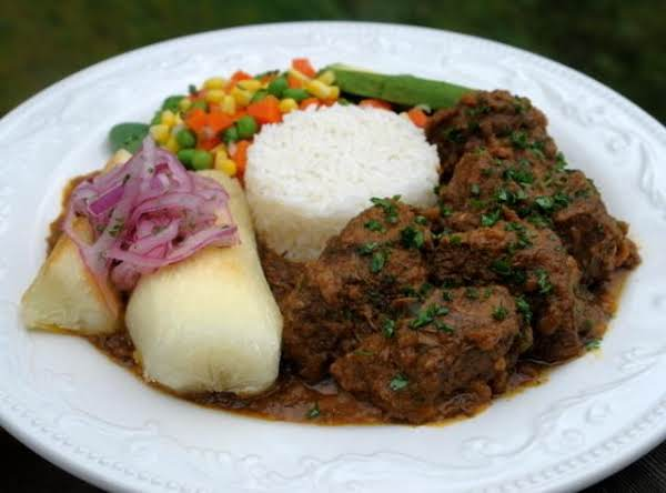 Lamb Stew Served With Rice And Yucca And A Vegetable
