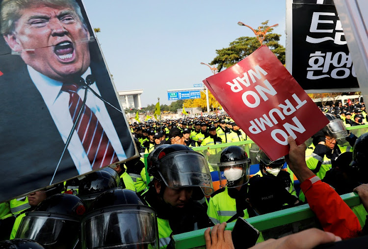 Anti-Trump protesters hold up signs in front of police officers near the South Korean National Assembly where US President Donald Trump made a speech, in Seoul, South Korea on November 8, 2017. REUTERS/KIM KYUNG-HOON