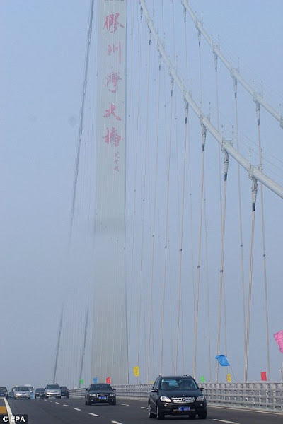 Photo: Open road : Drivers pass  through the mist as they make some of the first  passes over the 110ft wide bridge which is  longer than any others of its  kind.