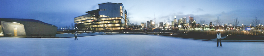 Photo: Pan of the open air lakeside ice ring looking toward the skyline of Toronto