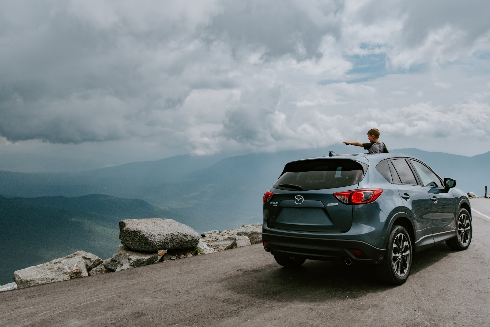kid in grey Mazda on road trip mountains