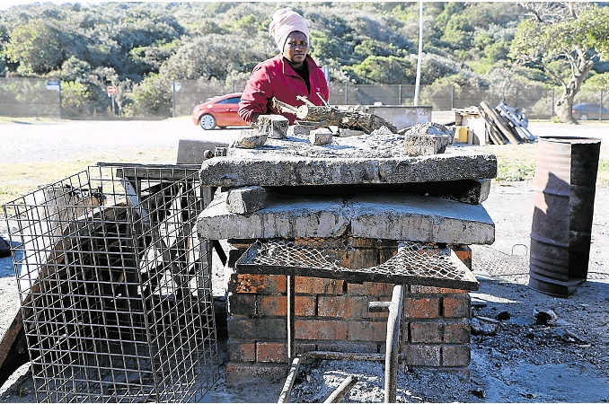 Ebuhlanti vendor Khulukazi Plati prepares fire to braai meat at her structure at the popular East London hangout spot.