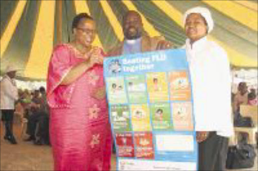 KNOWLEDGE IS POWER: The KwaZulu-Natal heath department has embarked on a campaign to educate people on how to curb the spread of the H1N1 influenza virus. From left: Health department head Sibongile Zungu with Reverend Bhekubuhle Dlamini and his wife Sindisiwe, at Newtown B in Inanda. PIC: THEMBA MNGOMEZULU. 07/09/2009. © Sowetan.