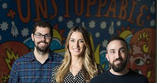 """RatedPower Founders in front of a colorful wall that says, """"Unstoppable""""."""