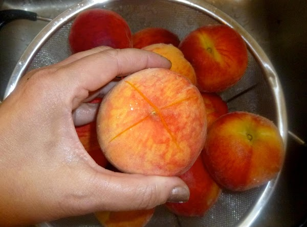 Rinse peaches thoroughly and cut away any bruises. Score the bottom of each peach...