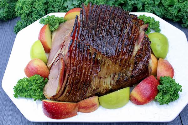 Baked Ham With Brown Sugar And Mustard Glaze On A Platter With Apples.