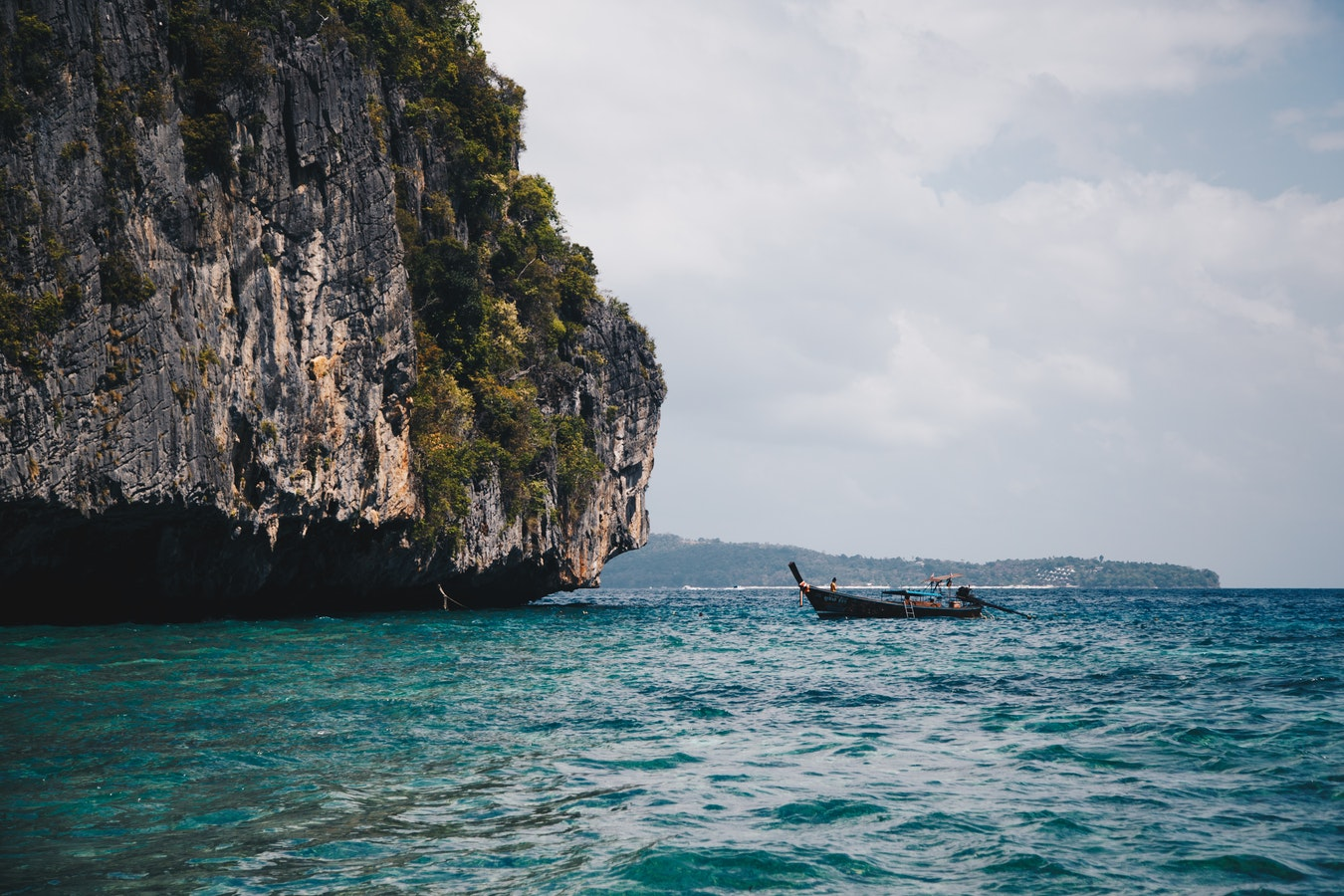 Boat on the water near brown rock formation during daytime, Krabi travel guide