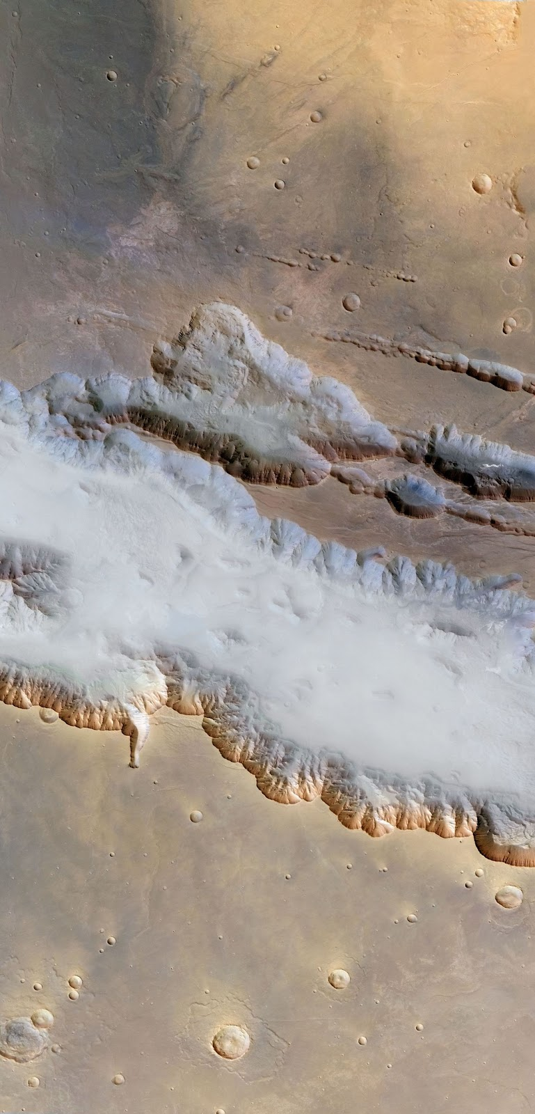 Туманы марсианской долины. Западная часть каньона Валлес Маринес, ширина которого составляет 3 060 км, на фотографии предстает покрытой дымкой водяного тумана и коркой утреннего водяного льда. В некоторых точках глубина каньона достигает 6,5 км, что более чем в три раза глубже Гранд Каньона в Аризоне на Земле