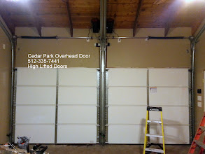 Photo: Two High Lifted and Follow the roof pitch doors. Note how the doors go up the wall and then follow the roof up. This keeps the door out of the way inside the facililty. Alos note the the door operators are mounted on the roof. There are no rails in the center of the room for the operators. If you need the inside of your room to be clear of the garage door, we can do that. Give us a call at 512-335-7441. Cedar Park Overhead doors. For garage door techies: Note the RAM Track, High lift, Follow the roof pitch. Also note the 8500 operators and the sprocket connections to the torsion tube.