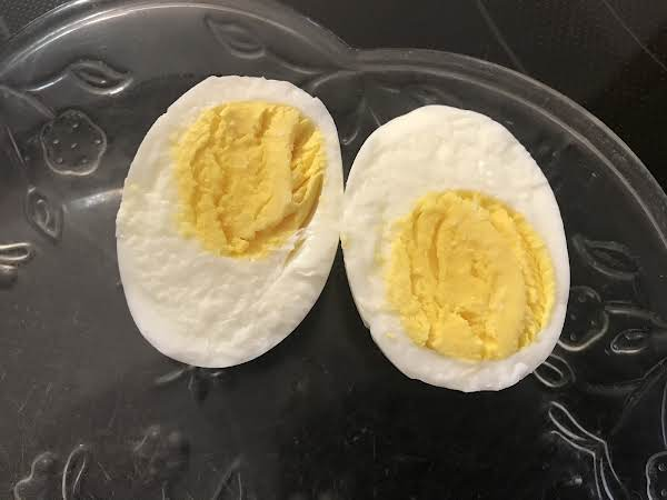 Cooked Egg, Cut In Half, Revealing Cooked Bright Yellow Yolks.