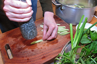 Photo: crushing cut lemon grass and layering on the bottom of a pot with torn kaffir lime leaves
