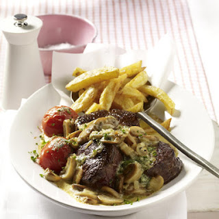 Steak with Mushroom Sauce, French Fries and Roasted Tomatoes.