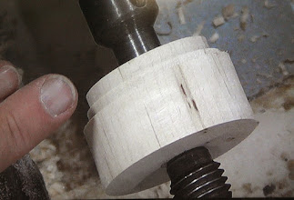 Photo: What's this?  Mark has moved the piece to a second center at a slight distance from the first and turned a second tenon on this new axis.  He now has the ability to mount this little homemade jam chuck for the finial later in his scroll chuck at two different angles.