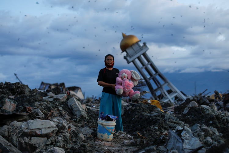 A woman holds a stuffed rabbit toy after it was found at her destroyed home, where she said she had lost her three children in Indonesia.