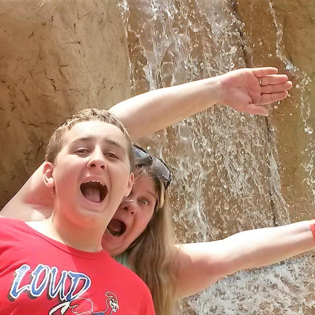 A woman and her son pose with in front of a waterfall and make funny faces with their mouths open