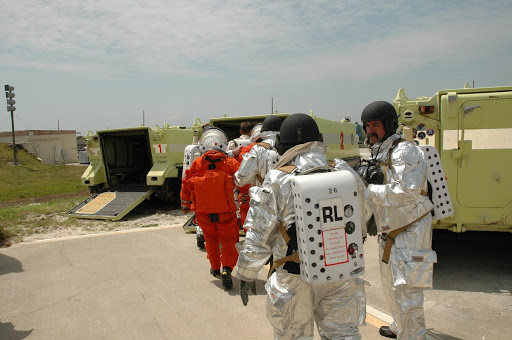 The KSC rescue team moves astronauts portrayed by KSC personnel into M-113 armored carriers.