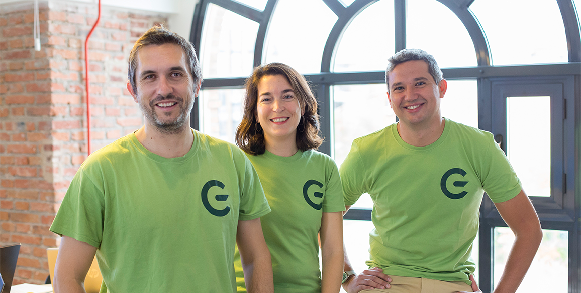 The GreeMko cofounders are wearing matching green shirts with their startups' logo and smiling at the camera.