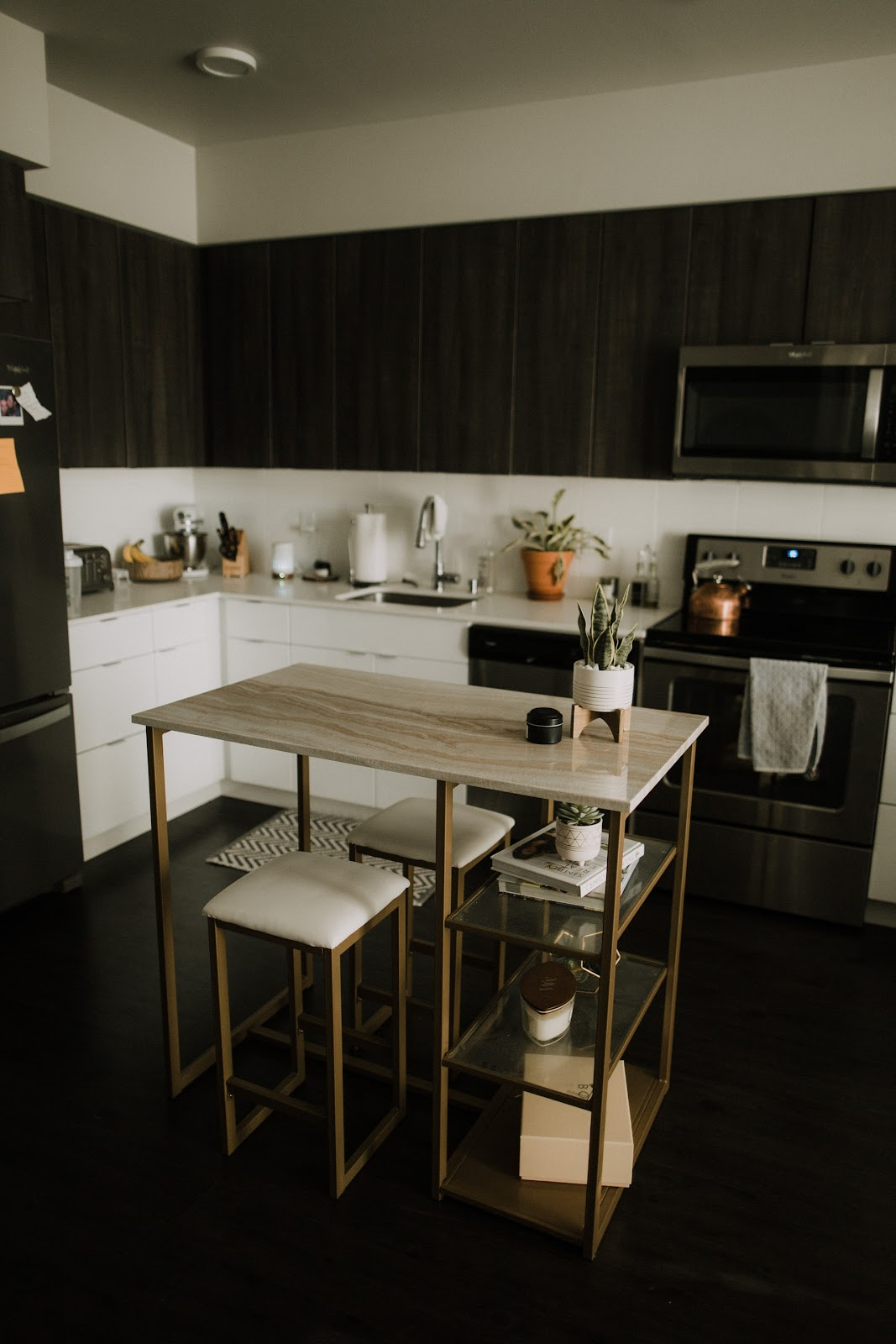 Compact kitchen with white and black wooden cabinets, and other essential utensils in the background