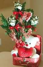 Photo: Design is done with 3 long stemmed roses, kisses (candy), balloon, vase of treats, & cuddly bear