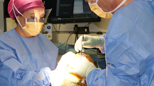 Dr McCready (right) explains that the robotic-assisted surgical system enhances surgical precision as it draws data from a CT scan of the patient's knee.