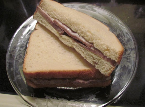 Top the meat with the other slice of bread forming a sandwich. Cut the...